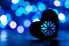 La silhouette du coeur avec la guirlande s'allume sur le fond bleu de bokeh Photos stock