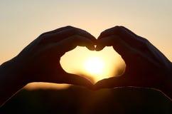 La silhouette du coeur des mains au centre de son Sun Le concept de l'amour et du bonheur Image libre de droits