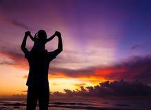 La silhouette du famille observant le lever de soleil Photo stock