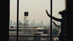 La silhouette du film de observation de jeune homme dans le casque de VR et ont l'expérience de réalité virtuelle sur le balcon d image libre de droits