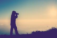 La silhouette du foyer debout de photographe féminin pour prennent un phot Photos stock