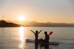 La silhouette du garçon de bonheur et la fille s'asseyant sur la petite gorgée surfent à l'océan Mode de vie de concept, sport, a Images libres de droits