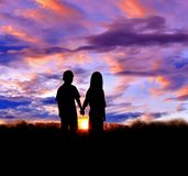 La silhouette du garçon et la fille se tiennent de pair pour observer le coucher du soleil Photos stock