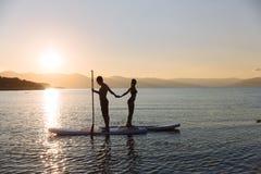 La silhouette du garçon et la fille sur le ressac de petite gorgée rassemblent des mains à l'océan Mode de vie de concept, sport, Photos stock