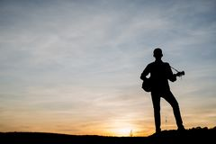 La silhouette du joueur de guitare sautent sur la pierre Photographie stock libre de droits