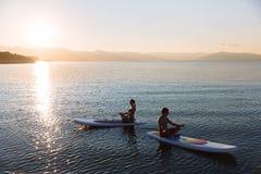 La silhouette du mâle et la femelle dans le yoga posent sur la natation de ressac de petite gorgée à l'océan Mode de vie de conce Image libre de droits