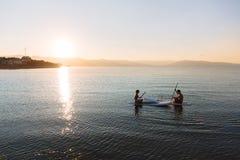La silhouette du mâle et la femelle dans le yoga posent sur la natation de ressac de petite gorgée à l'océan Mode de vie de conce Photos libres de droits