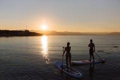 La silhouette du mâle et la femelle sur la petite gorgée surfent la natation à l'océan Mode de vie de concept, sport, amour Image stock