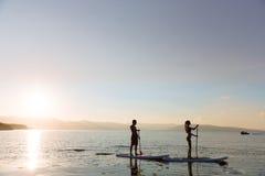 La silhouette du mâle et la femelle sur la petite gorgée surfent la natation à l'océan Mode de vie de concept, sport, amour Photos stock