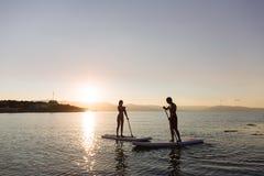 La silhouette du mâle et la femelle sur la petite gorgée surfent la natation à l'océan Mode de vie de concept, sport, amour Photo stock