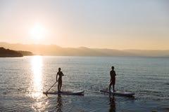 La silhouette du mâle et la femelle sur la petite gorgée surfent la natation à l'océan Mode de vie de concept, sport, amour Images libres de droits
