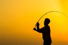 La silhouette du pêcheur sur la plage Photos stock