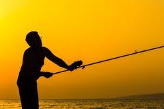 La silhouette du pêcheur sur la plage Photo libre de droits
