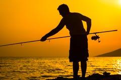 La silhouette du pêcheur sur la plage Photographie stock libre de droits