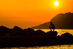La silhouette du pêcheur sur la plage Photo stock