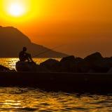 La silhouette du pêcheur sur la plage Images stock