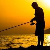 La silhouette du pêcheur sur la plage Images libres de droits
