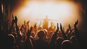 La silhouette du soliste/du chanteur se tient dans un brouillard dans les rayons de la lumière Foule de concert devant les lumièr Images stock