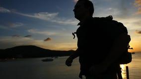 La silhouette du voyageur avec un sac à dos est arrivée sur la jetée pendant le coucher du soleil impressionnant à la mer, mouvem clips vidéos