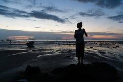 La silhouette femelle au coucher du soleil, femme se tient sur la plage de mer image stock