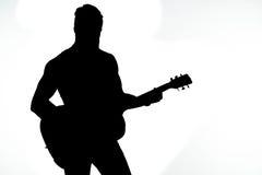 La silhouette noire d'un homme avec une guitare sur un blanc a isolé le fond Cadre horizontal Images stock