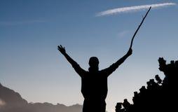 La silhouette noire d'une femme avec un bâton de marche dans sa main avec les bras augmentés copient l'espace Images stock