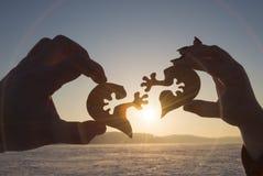 La silhouette relient le coeur deux morceaux de puzzle dans des mains des amants dans la perspective du lever de soleil photo stock