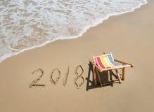 La silla de cubierta con 2018 escrito en arena escribe en la playa Fotografía de archivo