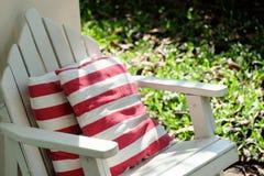 La silla de jardín con el respaldo rojo y blanco de la raya soporta Imagen de archivo