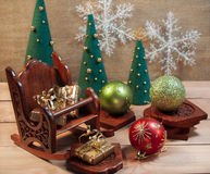 La silla de madera con los regalos acerca a árboles Fotos de archivo