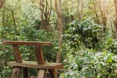 La silla de madera se deja en el jardín imagenes de archivo