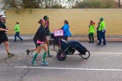 La silla de ruedas así que la persona discapacitada del empuje de tres mujeres pueden participar en carrera de día del St Patrick imagen de archivo libre de regalías