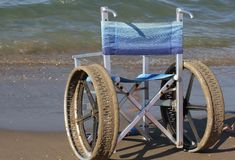 La silla de ruedas con acero inoxidable rueda para entrar adentro al mar Foto de archivo libre de regalías