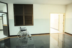 La silla de ruedas para los pacientes hace una pausa en el área común del pasillo del pasillo al lado de puerta de salida imagen de archivo