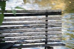 La silla larga de madera al lado del canal Butaca hecha por la madera de fotografía de archivo