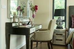 La silla marrón clásica con joyería fijó en el tocador Foto de archivo