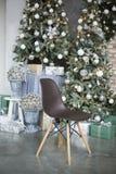 La silla marrón en costes de las piernas de madera en estudio contra la perspectiva de los conos verdes adornados del árbol de na imágenes de archivo libres de regalías
