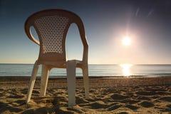 La silla plástica se coloca de lado en la playa cerca del mar Imagenes de archivo