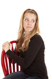 La silla roja de la muchacha piensa mirada detrás Foto de archivo libre de regalías