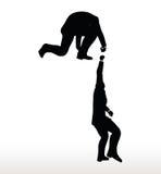 la silueta de dos hombres de negocios combina sostenerse encendido con una mano amiga Imagen de archivo libre de regalías