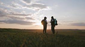 La silueta de dos mangos en el top de la monta?a con las mochilas y del otro engranaje que expresa energ?a y felicidad Dos metrajes