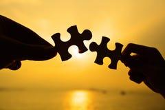 La silueta de dos manos conecta el rompecabezas junta Imagenes de archivo