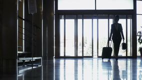 La silueta de la empresaria elegante con la maleta acaba de llegar en un hotel almacen de video