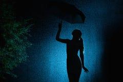 La silueta de la figura de una chica joven con un paraguas bajo la lluvia, una mujer joven con el pelo recogido a mano es feliz a imágenes de archivo libres de regalías