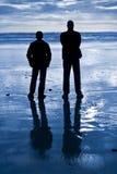 La silueta de hombres mira hacia fuera el océano Foto de archivo libre de regalías