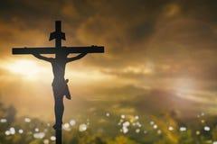 La silueta de Jesús con cruza encima el concepto de la puesta del sol para la religión Imágenes de archivo libres de regalías