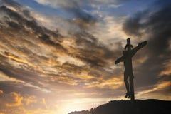 La silueta de Jesús con cruza encima el concepto de la puesta del sol para la religión, Imagenes de archivo