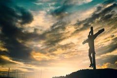 La silueta de Jesús con cruza encima el concepto de la puesta del sol para la religión, Foto de archivo libre de regalías