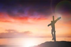 La silueta de Jesús con cruza encima el concepto de la puesta del sol para la religión, Fotos de archivo