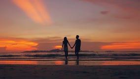 La silueta de la cámara lenta de pares cariñosos felices camina en la playa en puesta del sol en orilla del océano almacen de video